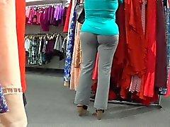 Sensual babe in gray pants walks around the store jiggling