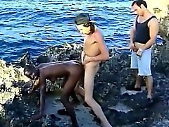 Black chick sucks white cocks and gets fucked on beach