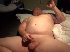 chubby tattooed guy with pierced dick jacks off to porn